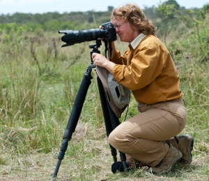 Image of Joyce Harmon peering through a camera on a tripod